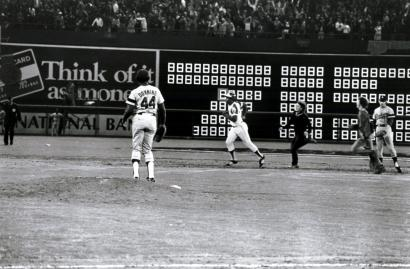 Dodgers pitcher Al Downing watches as Hank Aaron, trailed by two fans, runs out homer No. 715.